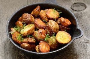 Roasted potato in a frying pan on wooden table